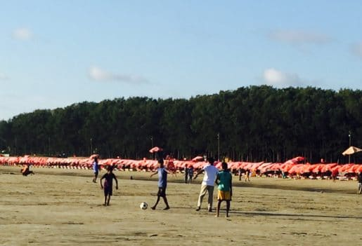 Red parasols and sunloungers Cox's Bazar Beach Bangladesh