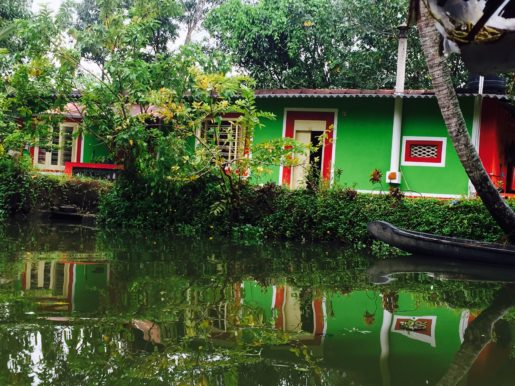 Brightly coloured house and reflections on Kerala backwaters