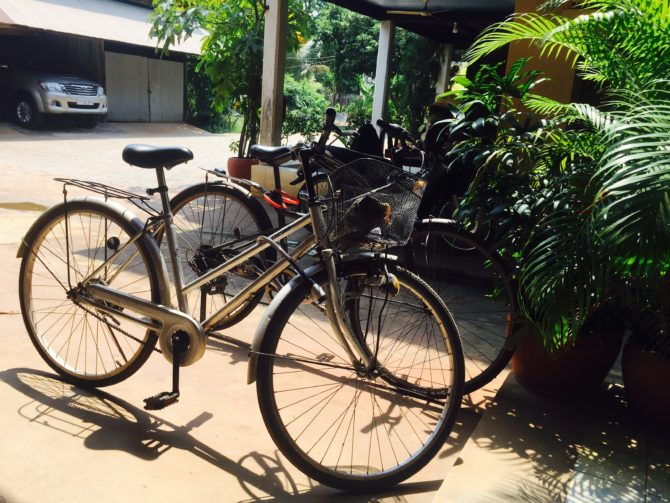Two push bikes outside a Khmer wooden house on stilts when living and working in Siem Reap Cambodia