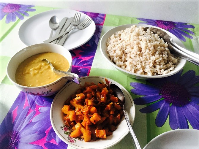 Bowls of rice, curry and lentil dahl.