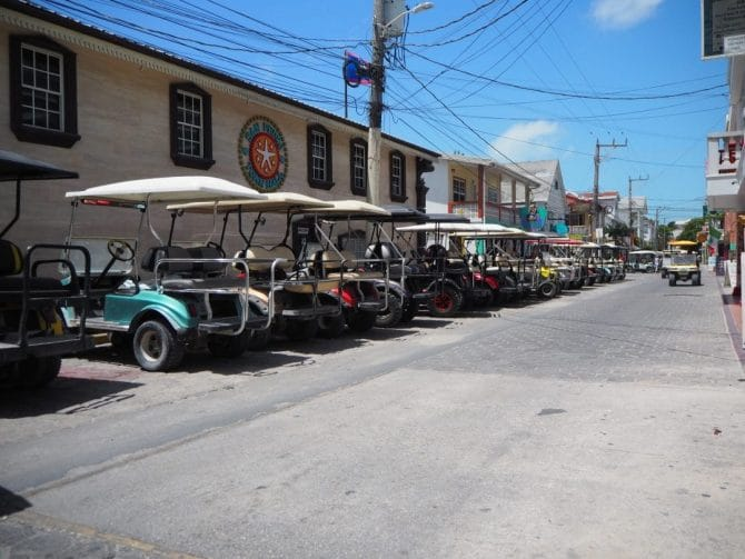 Golf carts lined up in the street in San Pedro, Belize