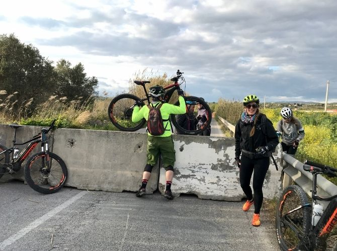 Lifting bikes over a blockade in Sicily.