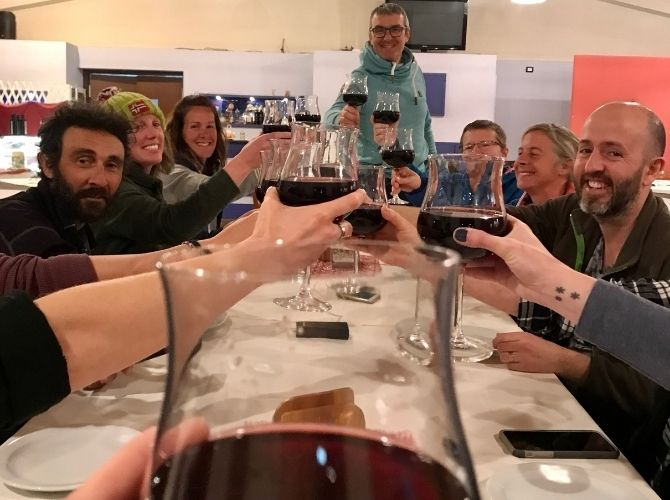 Group making a toast with red wine at the restaurant in Agritourismo Giannavi in Sicily