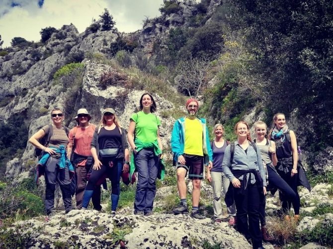 Small tour group standing on rocks in Pantalica, Anapo Valley in Sicily.
